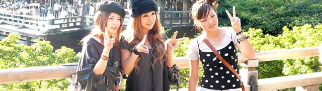 Three teenage girls in Japan dressed in western fashion and making 'peace' signs for their social media sites.