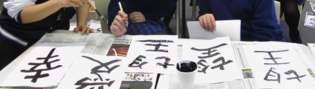 Anonymous students writing Japanese characters with brushes and ink.