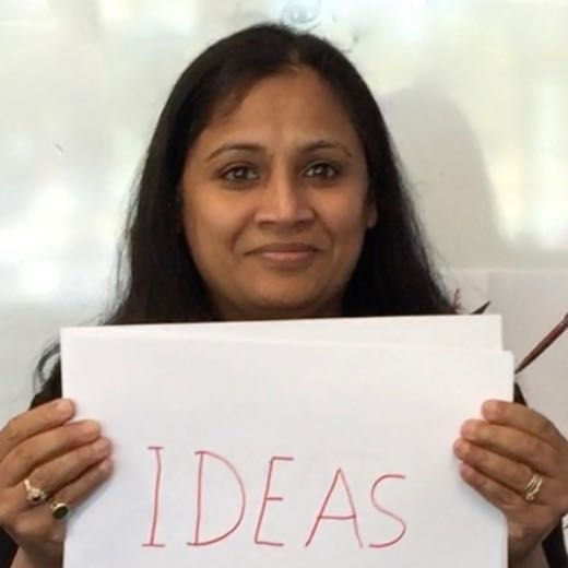 Rashmi holding asign saying 'ideas'.